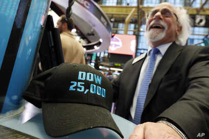 "FILE- Trader Peter Tuchman smiles as he poses with an old ""Dow 25,000"" hat on the New York Stock Exchange trading floor, Jan. 30, 2019."