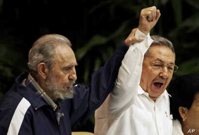 In this April 19, 2011 file photo, Fidel Castro, left, raises his brother's hand, Cuba's President Raul Castro, center, as they sing the anthem of international socialism during the 6th Communist Party Congress in Havana, Cuba.