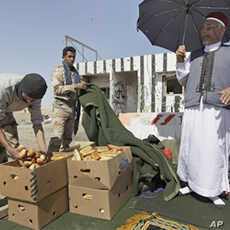Mohammed Tajouri, 54, a local elder, distributes bread to rebel fighters on the outskirts of Ajdabiya, Libya Thursday, April 14, 2011