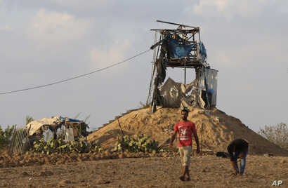 Palestinians inspect a military observation post that was hit by an Israeli tank shell east of Khan Younis, southern Gaza Strip, July 20, 2018. Israel pummeled Hamas targets in Gaza killing four Palestinians Friday in a series of air strikes after gu...