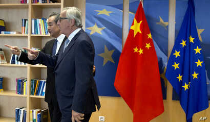 European Commission President Jean-Claude Juncker (R) speaks with China's Foreign Minister Wang Yi prior to a meeting at EU headquarters in Brussels, June 1, 2018, as the two sides deepen ties on trade and investment.
