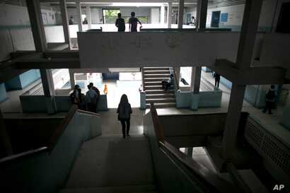 Students walk inside their public high school in Caracas, Venezuela, June 1, 2016. While the school locks its gate each morning, armed robbers still manage to infiltrate and stick up kids between classes.