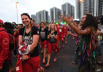 Members of Canada's Olympic team parade past dancers following a flag-raising ceremony at the Athletes Village in Rio de Janeiro, Brazil on Aug. 2, 2016.