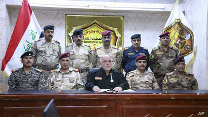 This photo released on his official Facebook page shows Iraqi Prime Minister Haider al-Abadi, center, surrounded by top military and police officers as he announces the start of the operation to liberate the northern city of Mosul from Islamic State ...
