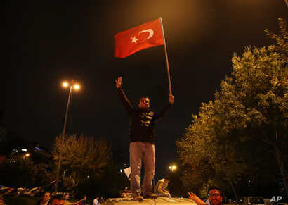 A supporter of Turkey's President Recep Tayyip Erdogan and The Justice and Development Party (AKP), waves a national flag as he celebrates outside the AKP headquarters, in Istanbul, Nov. 1, 2015.