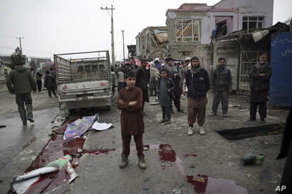 Residents walk through the site of a suicide attack in Kabul, Afghanistan, March 2, 2018. A large explosion in the eastern part of the Afghan capital on Friday morning killed at least one and wounding others officials said.
