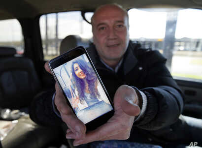 Motaz Alafandi of Syria shows a photo he keeps on his smartphone of his daughter Yara, 18, who lives in Montreal, Jan. 27, 2017, in Garland, Texas. Alafandi, a 49-year-old Syrian lives in Dallas while seeking asylum with his wife and three youngest c...