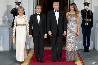 President Donald Trump, first lady Melania Trump, French President Emmanuel Macron and his wife Brigitte Macron, pose for photographs as they arrive for a State Dinner at the White House in Washington, April 24, 2018.