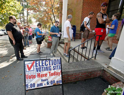 People arrive to cast their ballot for 2016 elections at a polling station as early voting begins in North Carolina, in Carrboro, North Carolina, Oct. 20, 2016.