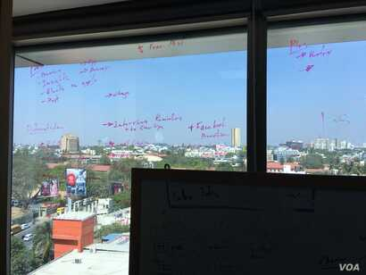 Babajob employees take notes on a window overlooking a neighborhood in downtown Bangalore. (E. Sarai/VOA)