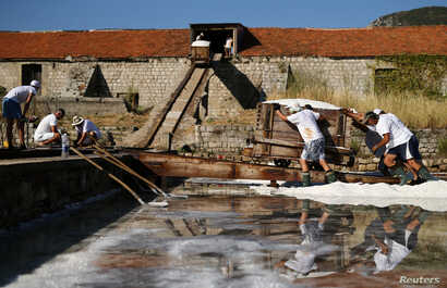 Workers push wagons full of salt at the Ston Saltworks site in Ston, Croatia, Aug. 8, 2017.