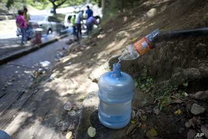 A water bottle is used as a funnel to fill a large container with water trickling from a hillside spring, during water shortages in Caracas, Venezuela, June 14, 2018.