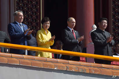 FILE - Chinese President Xi Jinping, right, applauds with, from left, Kazakhstan President Nursultan Nazarbayev, South Korea President Park Geun-hye and Russia's President Vladimir Putin, during a parade to mark the 70th anniversary of Japan's surren...