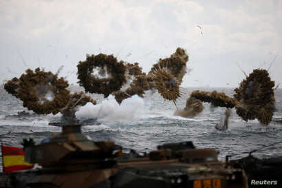 FILE - Amphibious assault vehicles of the South Korean Marine Corps fire smoke bombs as they move to land on the shore during a U.S.-South Korea joint landing operation drill as a part of the two countries' annual military training called Foal Eagle,...
