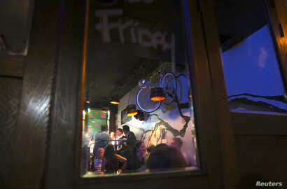 FILE - Patrons are reflected in a mirror as they drink in the York Lane Bar located in Sydney, Australia.
