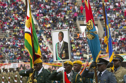 Soldiers carry a portrait of Zimbabwe's President Robert Mugabe during the country's 37th Independence celebrations in Harare, April, 18, 2017.