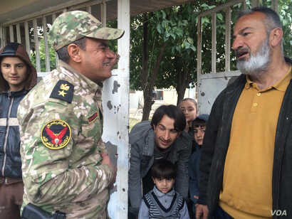 Colonel Abdulamir Al-Muhammadawi of the Iraqi army's Rapid Response Unit greets residents in al-Josaq neighborhood in western Mosul, who largely stay in their homes because of ongoing sniper fire, March 2, 2017. (H. Murdock/VOA)