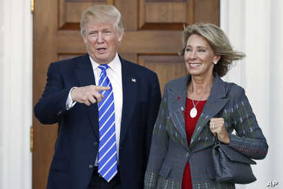 President-elect Donald Trump, left, and Betsy DeVos, right, pose for photographs at Trump National Golf Club Bedminster's clubhouse in Bedminster, N.J.