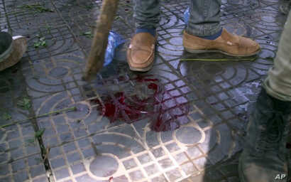 In this image made from video, blood is seen on the ground after an explosion at a rally for Ethiopia's new prime minister, in Addis Ababa, Ethiopia, June 23, 2018.