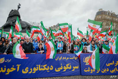 People hold a banner and wave former Iranian flags during a demonstration of the exiled Iranian opposition to protest against the celebration in Iran of the 40th anniversary of the Islamic Revolution, Feb. 8, 2019 in Paris, France.
