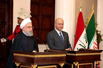Iraqi President Barham Salih, right, and Iranian President Hassan Rouhani hold a press conference at Salam Palace in Baghdad, Iraq,  March 11, 2019.
