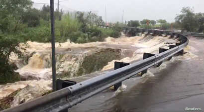 Flood waters cascade down a road in Hilo, Hawaii, Aug. 24, 2018, in this still image taken from a video obtained from social media.