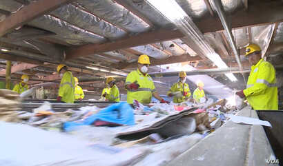 At Duong's recycling facility, employees and complex machines now do the sorting his family once did by hand.