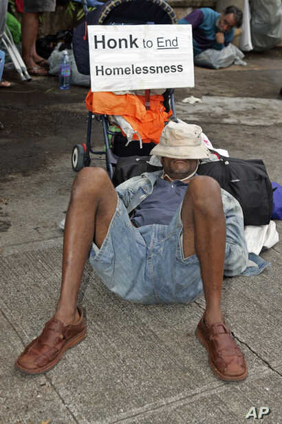 A man sleeps on the sidewalk in front of Honolulu Hale, Tuesday, March 28, 2006, in Honolulu after the City evicted groups of homeless people from Ala Moana beach park in order to begin renovations to park facilities.