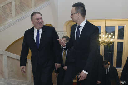 U.S. Secretary of State, Mike Pompeo, left, and Hungary's Minister for Foreign Affairs and Trade, Peter Szijjarto, chat during talks in Budapest, Hungary, Feb. 11, 2019