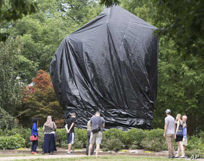 Residents and visitors look over the covered statue of Confederate General Robert E. Lee in Emancipation park in Charlottesville, Va., Aug. 23, 2017. The move to cover the statues is intended to symbolize the city's mourning for Heather Heyer, killed