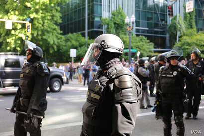 """Armed police officers fill downtown Portland, near City Hall, during rival """"anti-hate"""" and """"free speech"""" rallies, June 4, 2017."""