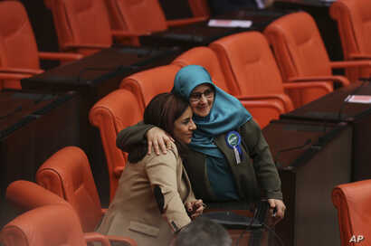 FILE - Huda Kaya (R), a legislator with pro-Kurdish Peoples' Democratic Party, (HDP), embraces Selina Dogan (L), of main opposition Republican People's Party (CHP), in the parliament in Ankara prior to deliberations over a controversial package of co...