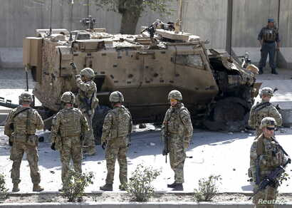 FILE - NATO soldiers stand near a damaged NATO military vehicle at the site of a suicide car bomb blast in Kabul, Afghanistan, Oct. 11, 2015.