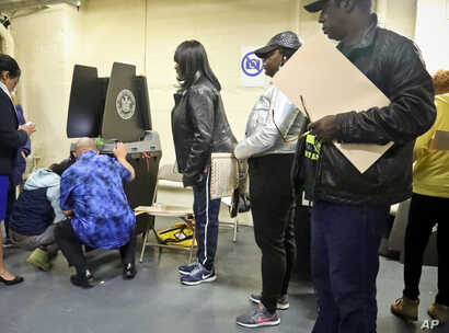 Polling site officials, left, check on a voting scanner after it jammed, forcing voters to manually file their ballots until a repair was made, Tuesday Nov. 6, 2018, in the Parkchester community of the Bronx borough of New York.