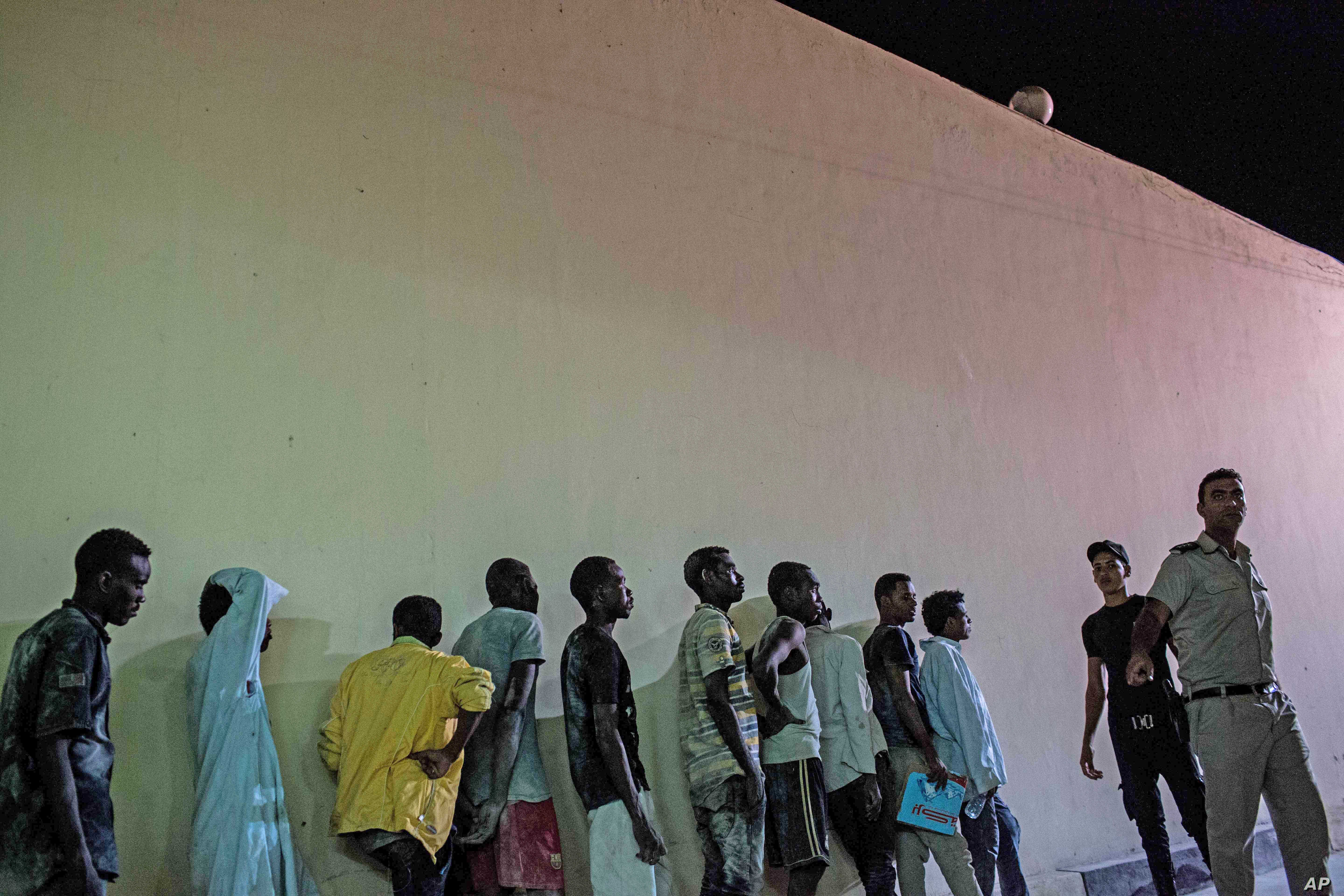 Security officers line up Sudanese people detained at a police station in Rosetta, Egypt, after rescued from a boat capsized off the Mediterranean coast near the Egyptian city of Alexandria, Sept. 21, 2016.