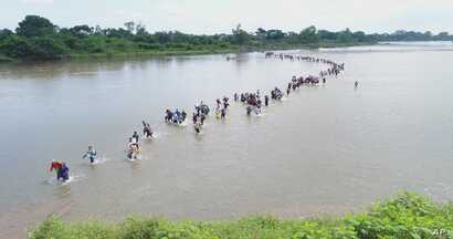 FILE - Salvadoran migrants cross the Suchiate River near Tecun Uman, Guatemala, the border with Mexico, Nov. 2, 2018, as the caravan of Central American migrants make its way north, hoping to enter the United States.