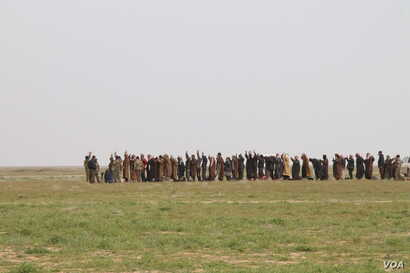 Men line up to be searched and then investigated for suspected connections to the Islamic State group after leaving the battle for IS's last stronghold, which is not much more than a camp along the banks of the Euphrates River, picture taken Feb. 26,...