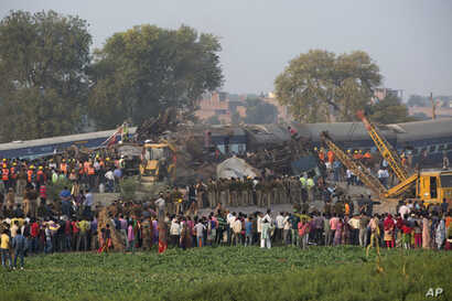 People gather as rescuers work after 14 coaches of an overnight passenger train rolled off the track near Pukhrayan village Kanpur Dehat district, Uttar Pradesh state, India, Nov. 20, 2016.