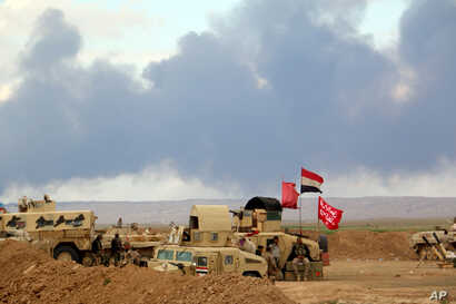 Smoke rises as the Iraqi army, supported by volunteers, battles Islamic State extremists outside Tikrit, March 4, 2015.