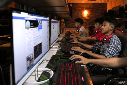 FILE - This picture taken on Dec. 18, 2018 shows Myanmar youths browsing their Facebook page at an internet shop in Yangon.
