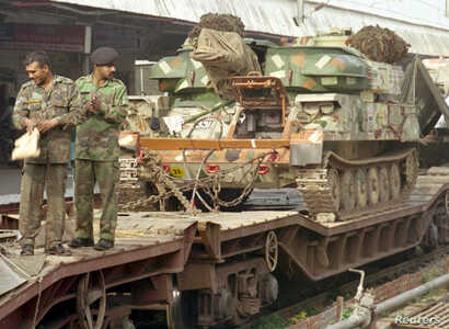 FILE - Indian soldiers stand in front of a tank being transported on a railcar at a station in Ambala, Dec. 30, 2001. India and Pakistan massed troops along their borders in the biggest such buildup in 15 years following the Dec. 13 attack on the Ind...