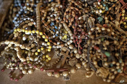 A pile of necklaces and crucifixes belonging to some of those who were slaughtered as they sought refuge inside the church sit on the altar as a memorial to the thousands who were killed during the 1994 genocide in Rwanda.