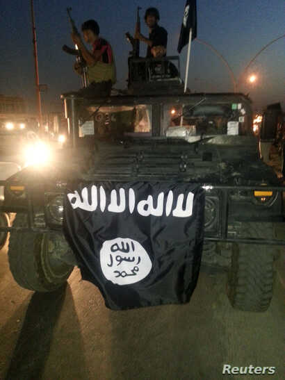 FILE - Islamic State display their flag during celebrations in Mosul, Iraq.