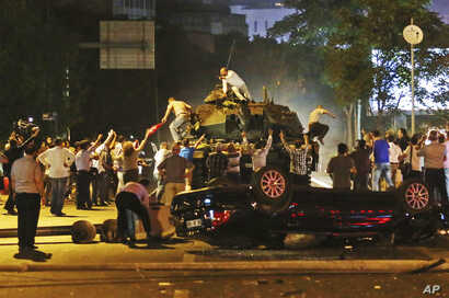 Tanks move into position as Turkish people attempt to stop them, in Ankara, Turkey, early Saturday, July 16, 2016.