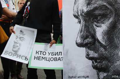 Anti-government protesters hold posters asking who killed opposition leader Boris Nemtsov as they march during an opposition rally in Moscow, Russia, on Sunday, Sept. 20, 2015. (photo by M. Eckels)