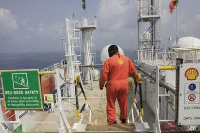 A Shell employee is seen aboard an oil vessel off the coast of Nigeria in this December 26, 2011, file photo.