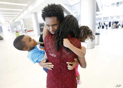 Olympic silver medalist Feyisa Lilesa, rear, of Ethiopia, hugs his wife Iftu Mulia, his daughter Soko, right, 5, and son Sora, left, 3, while picking up his family at Miami International Airport, Feb. 14, 2017.