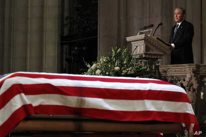 =Former President George W. Bush speaks in front of the flag-draped casket of his father, former President George H.W. Bush, at the State Funeral at the National Cathedral, Dec. 5, 2018, in Washington.