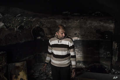 Mustafa Ismael Mustafa stands in his burned house as he returned home, March 29, 2017, after the neighborhood was retaken by Iraqi security forces during fighting with Islamic State militants, on the western side of Mosul, Iraq.