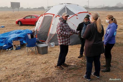 Randy Greb, who lost his house in Paradise in the Camp Fire, talks with employees of the Butte County Department of Employment and Social Services near his tent in a makeshift evacuation center in Chico, Calif., Nov.  16, 2018.